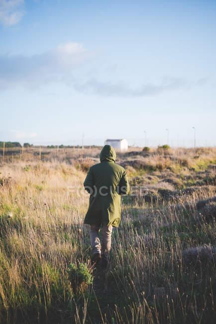 Vista posteriore dell'uomo che cammina attraverso il campo — Foto stock