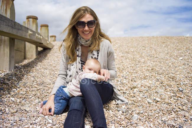 Мати з дитиною дівчина сидить на гальці пляж дивлячись на камеру посміхаючись — стокове фото