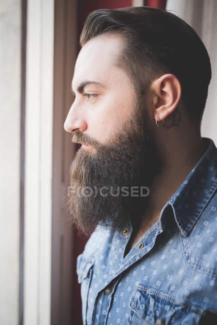 Молодой бородатый мужчина смотрит в окно — стоковое фото