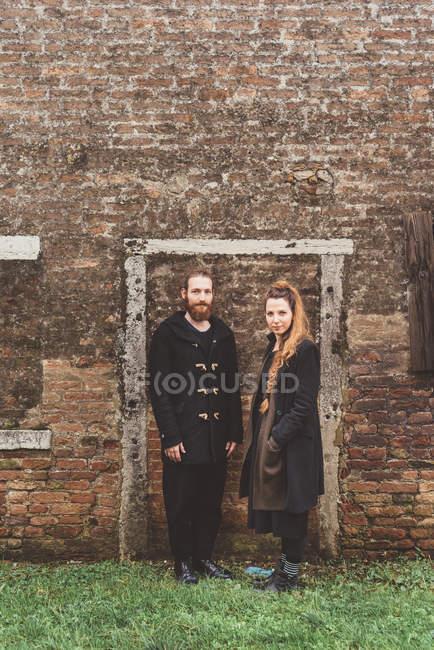 Portrait de couple en face de l'ancien cadre de porte de mur de brique — Photo de stock