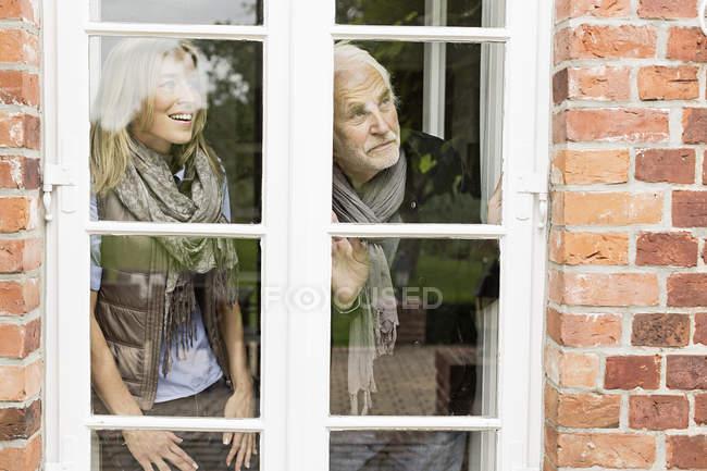 Vater und Tochter blicken durch Fenster — Stockfoto