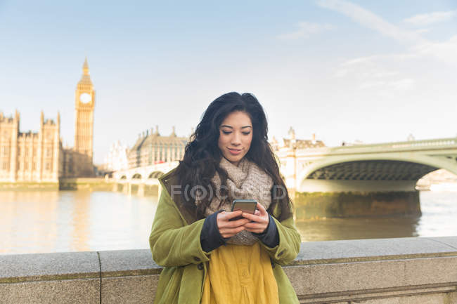 Young woman in front of Westminster bridge and Big Ben looking down using smartphone, Thames river, London, UK — Stock Photo