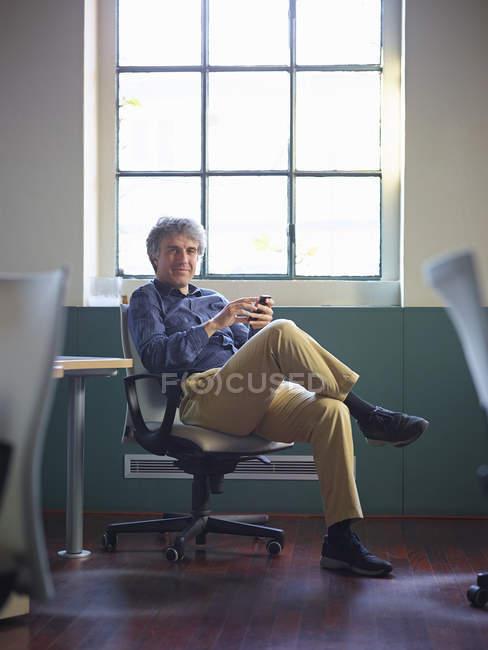 Зрілий бізнесмен сидить на офісному кріслі з мобільного телефону — стокове фото