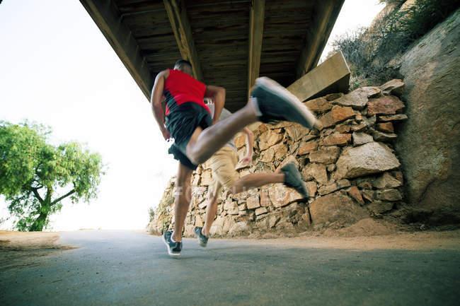 Dois amigos do sexo masculino, correndo sob ponte, visão traseira, visão de baixo ângulo — Fotografia de Stock