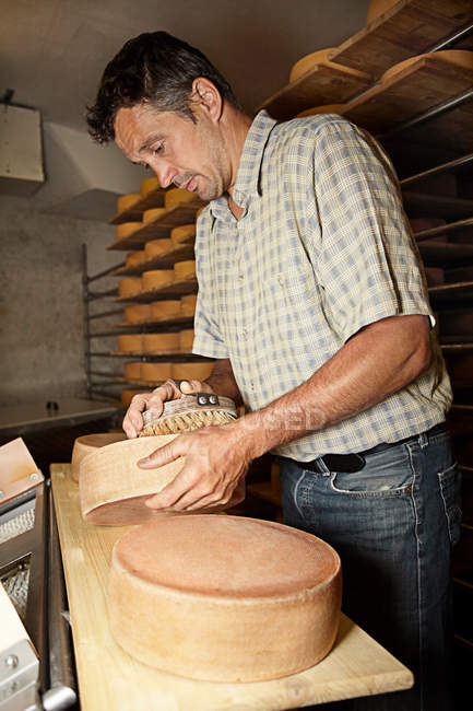 Worker finishing wheel of cheese in shop — Stock Photo
