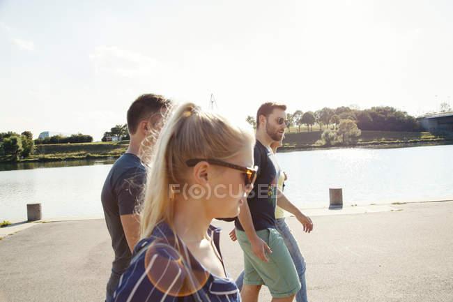 Cuatro jóvenes amigos caminando a orillas del río - foto de stock