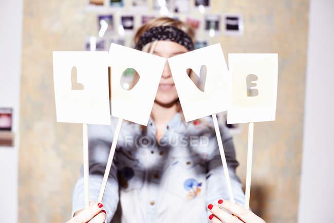 Молода жінка перед фото стіни ховається за любов'ю знак — стокове фото