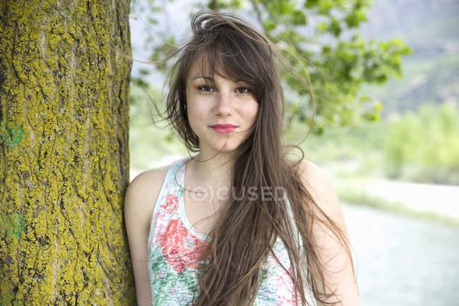 Porträt der jungen Frau Baumstamm gelehnt — Stockfoto
