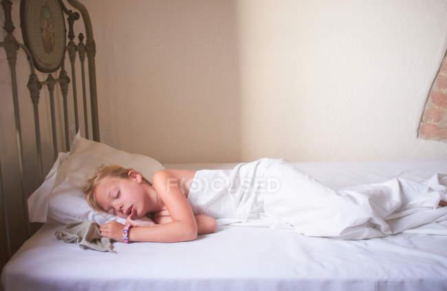 Девочка, спящая в постели — стоковое фото