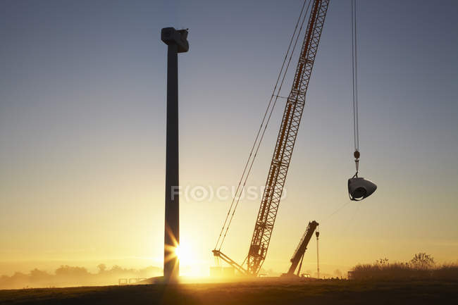 Erecting wind turbine and crane silhouettes on sunset sky — Stock Photo