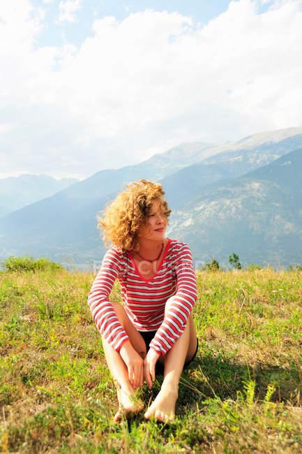 Mujer sentada en una colina rural - foto de stock