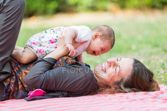 Mother lying down on blanket and holding baby girl — Stock Photo
