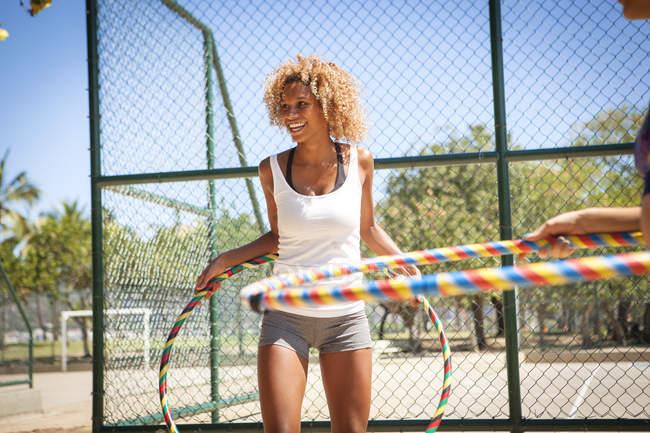 Молода жінка з Хула Хооп навколо талії, на відкритому повітрі — стокове фото