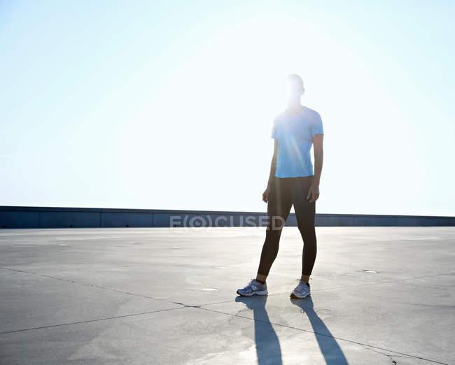 Coureur debout sur le toit le jour — Photo de stock