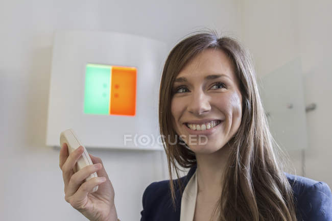 Woman in opticians office holding remote control looking away smiling — Stock Photo