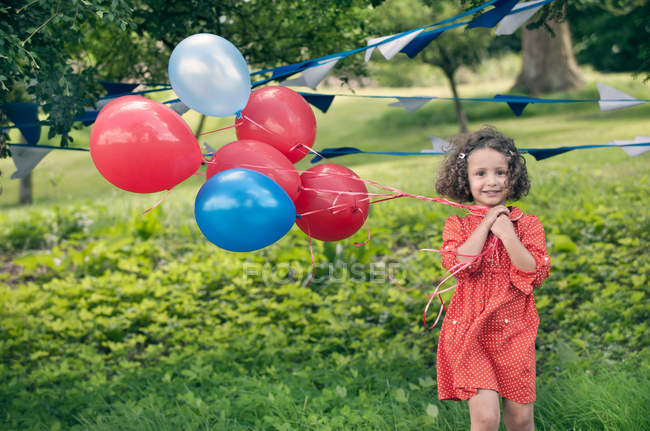 Girl holding bunch of balloons outdoors — Stock Photo
