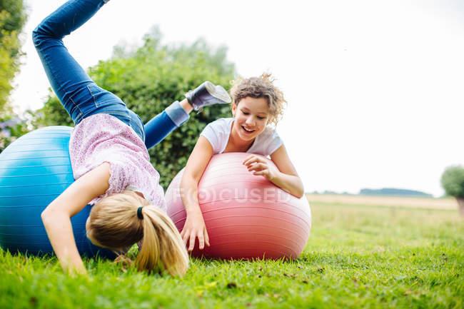 Due ragazze di tween scherzare su sfere di esercitazione nel giardino — Foto stock