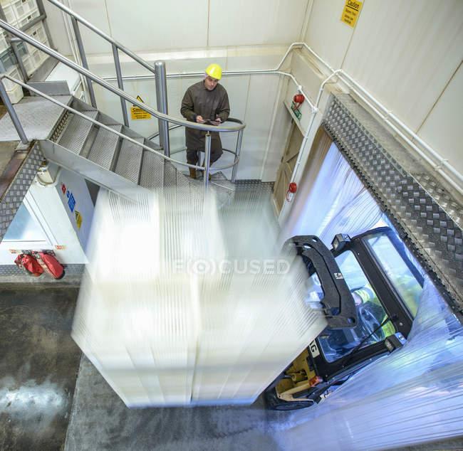 Працівник дивився вилка ліфт в навантажувальну затоку харчової фабрики — стокове фото