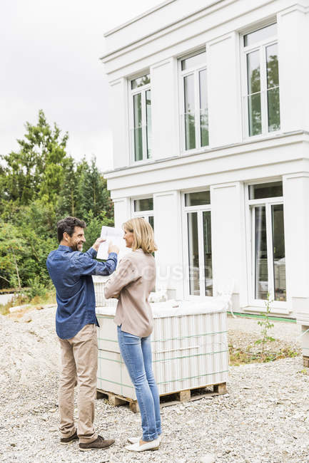 Full length rear view of architect discussing blueprints for house exterior with homeowner pointing — Stock Photo