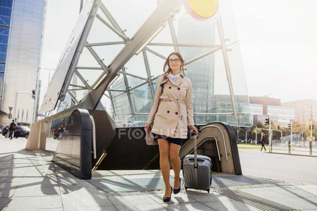 Empresaria con maleta de ruedas por escalera mecánica - foto de stock