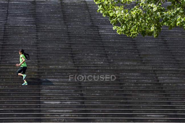 Женщины бегун, запуск по диагонали вверх деревянная лестница — стоковое фото