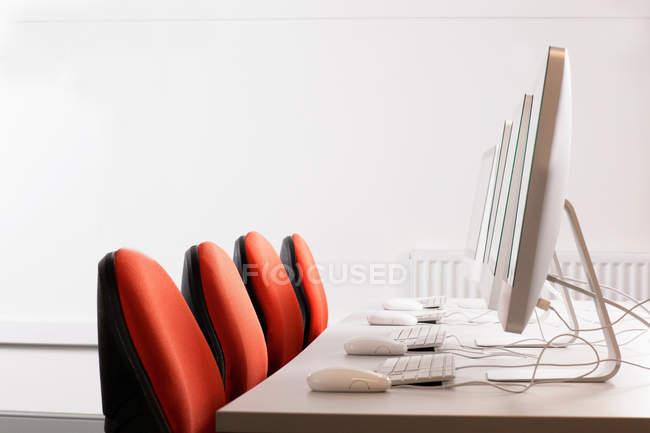 Computer und Stühle am Schreibtisch — Stockfoto