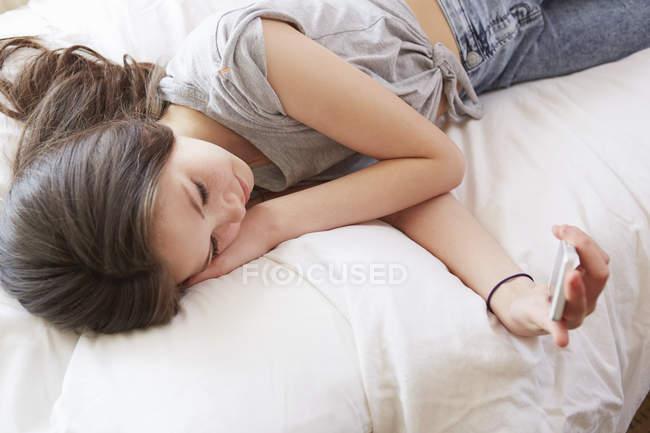 Blick auf das Mädchen, das auf dem Bett liegt und Smartphone-SMS liest — Stockfoto