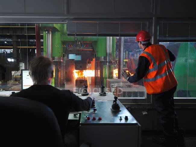 Инженеры в комнате управления стальной кузницей — стоковое фото