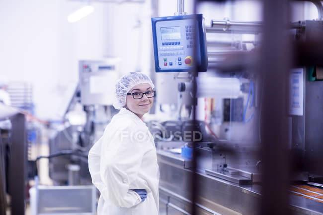 Робітниця заводу дивлячись через плече на камеру посміхається — стокове фото