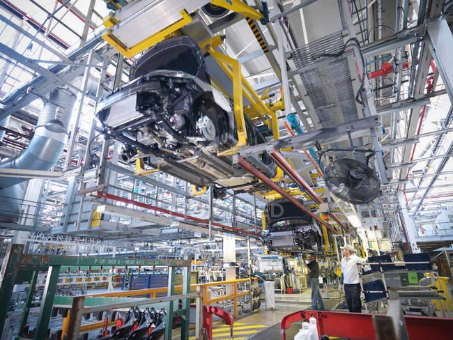 Рабочие на линии по производству автомобилей на автомобильном заводе — стоковое фото