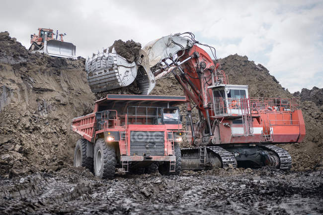 Large excavator and dumper truck in surface coal mine — Stock Photo