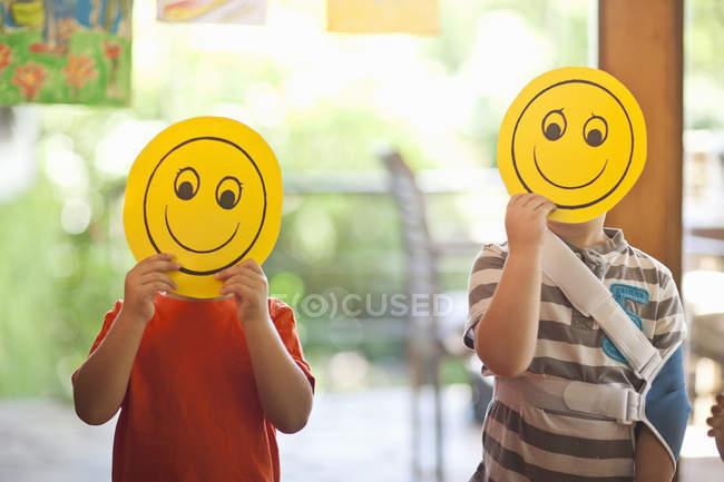 Deux garçons portant des masques souriants à l'école maternelle — Photo de stock