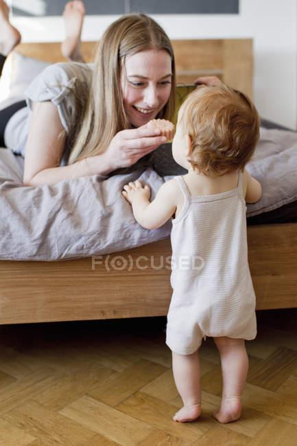 Середине взрослых женщина кормит дочь печенье от кровати — стоковое фото