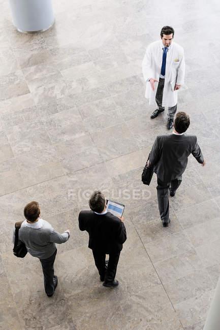 Geschäftsleute und Ärzte grüßen — Stockfoto