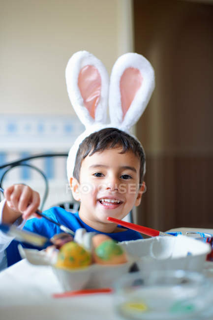 Boy wearing bunny ears painting Easter eggs — Stock Photo