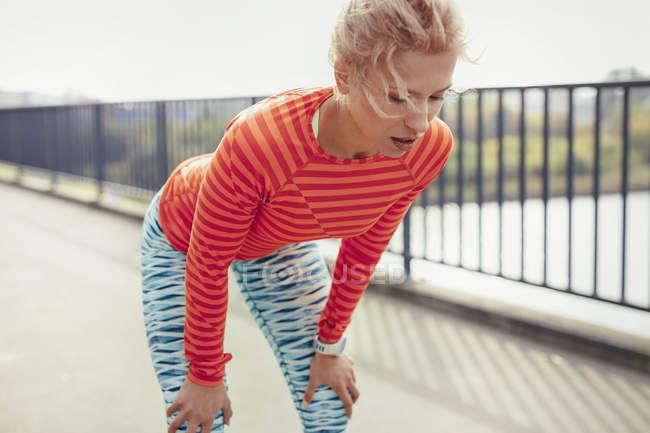 Jeune coureur féminin prenant une pause sur la passerelle de la ville — Photo de stock