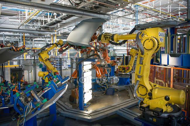 Robots handling car parts in car factory — Stock Photo