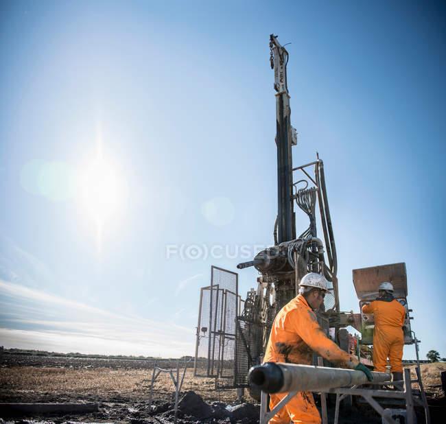 Travailleurs à la recherche de veines de charbon avec plate-forme de forage à la mine de charbon de surface — Photo de stock