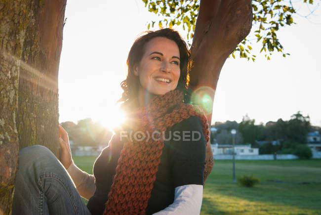 Mujer sentada en el árbol en el parque - foto de stock