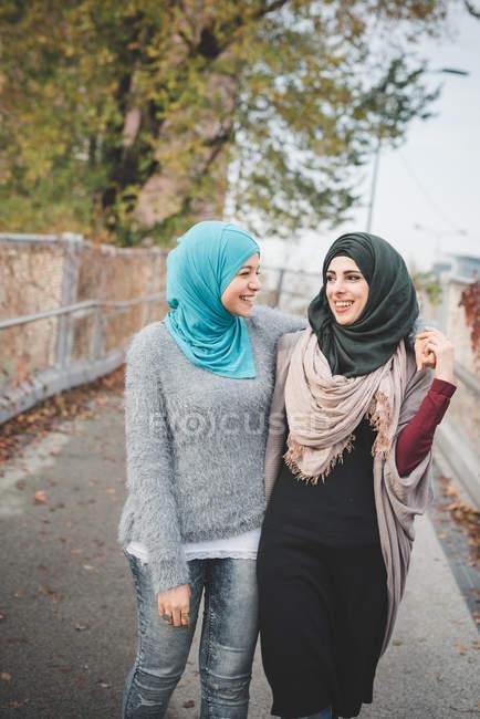 Dos amigas jóvenes caminando y charlando en el sendero del parque - foto de stock