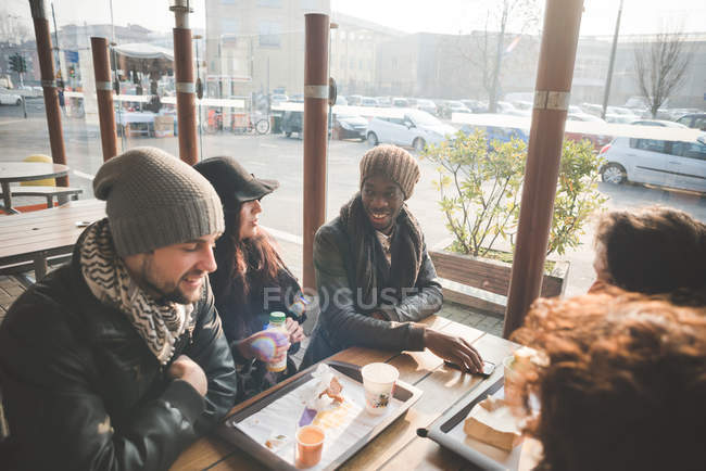 Five young adult friends chatting at sidewalk cafe — Stock Photo