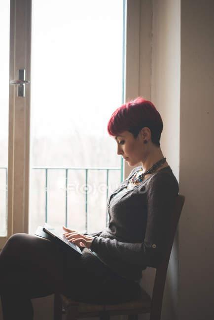 Jeune femme assise par la fenêtre, en utilisant une tablette numérique — Photo de stock