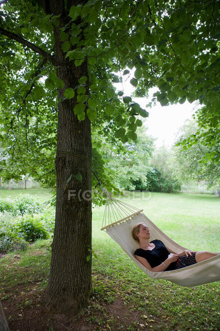 Woman relaxing in hammock outdoors — Stock Photo
