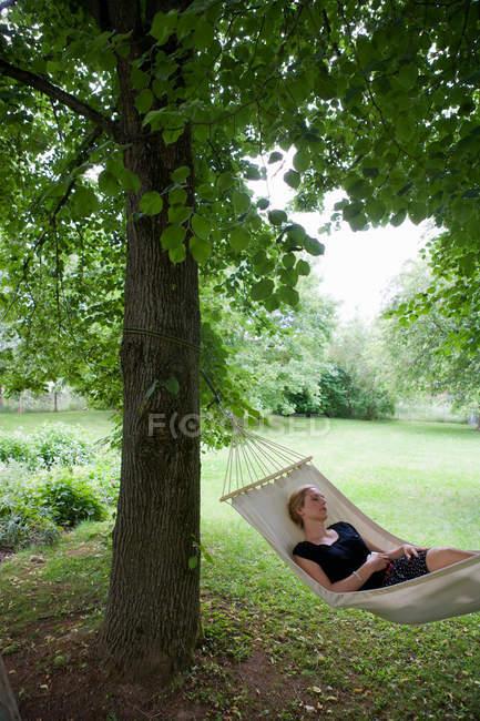 Женщина, отдохнуть в гамаке на открытом воздухе — стоковое фото