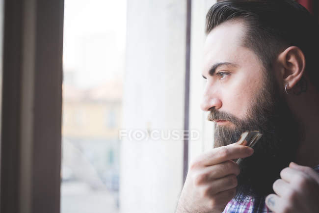 Young bearded man trimming his beard by window — Stock Photo