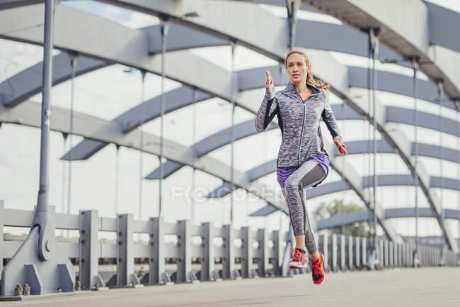 Female runner running at speed on city footbridge — Stock Photo
