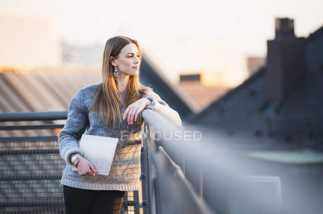 Young woman carrying digital tablet looking out from rooftop — Stock Photo