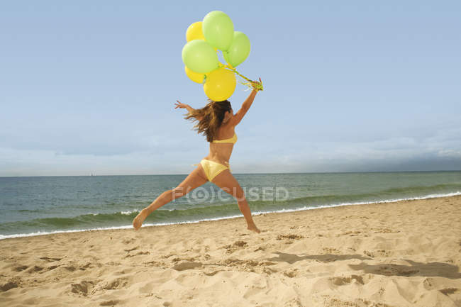 Woman jumping with balloons on beach — Stock Photo