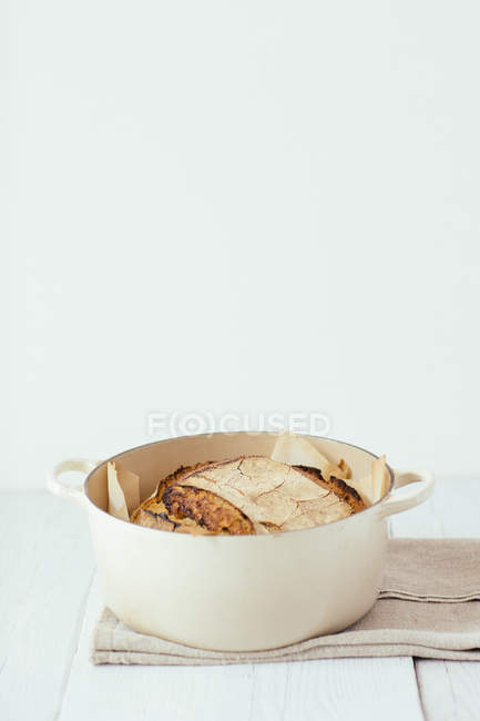 Saucepan with artisan sourdough bread on cloth napkin — Stock Photo