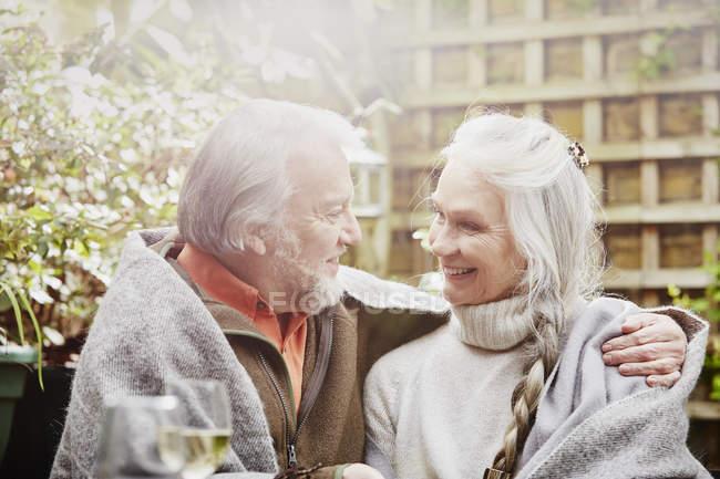Старшая пара, завернутая в одеяло в саду — стоковое фото
